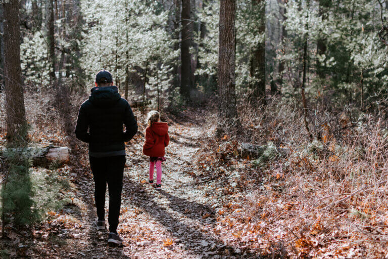 Father and daughter walking in a forest