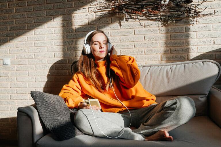 Woman relaxing on sofa wearing headphones