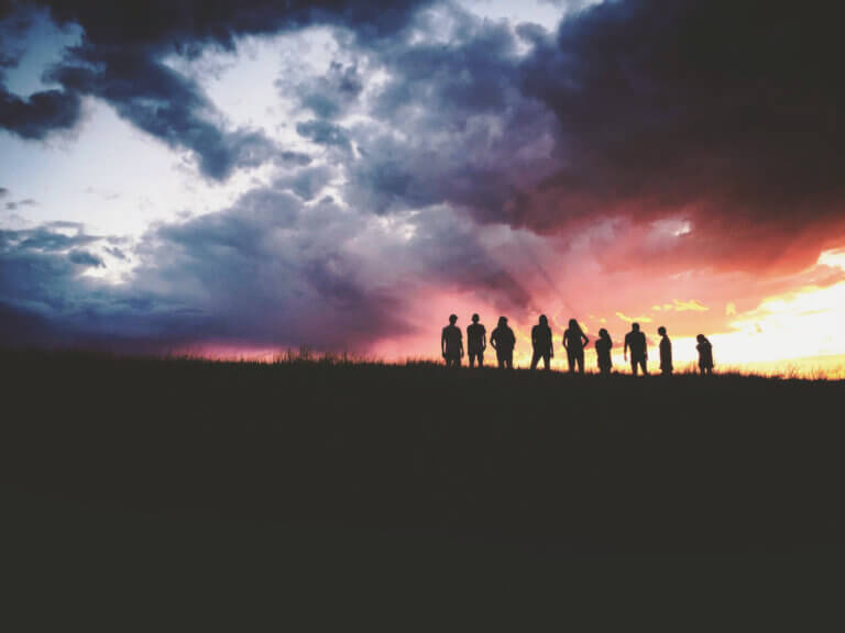 silhouettes of people with sunset and clouds in the background